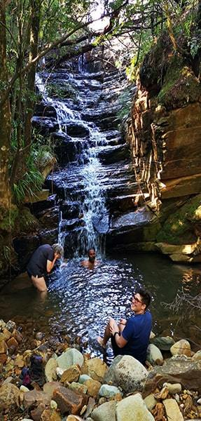 Hikers swimming in a natural pool below a waterfall